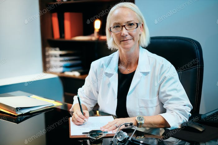 Portrait Of Female Doctor Working In Hospital Office Smiling At Camera