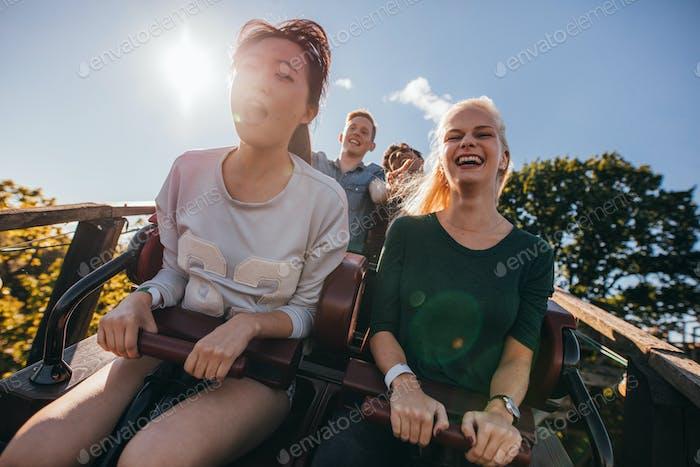 Begeisterte junge Freunde auf Achterbahnfahrt