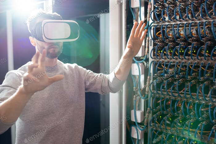 Engineer in VR goggles working in database center