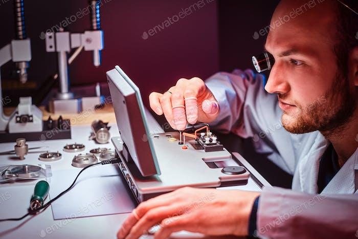 Fokussierter Uhrmacher arbeitet in seinem eigenen Atelier.