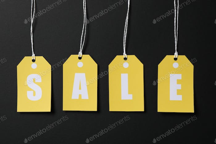 Inscription Sale on price tags on black background. Black Friday concept