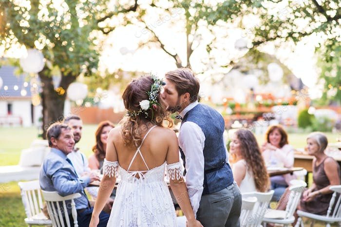 Bride and groom kissing at wedding reception outside in the backyard.