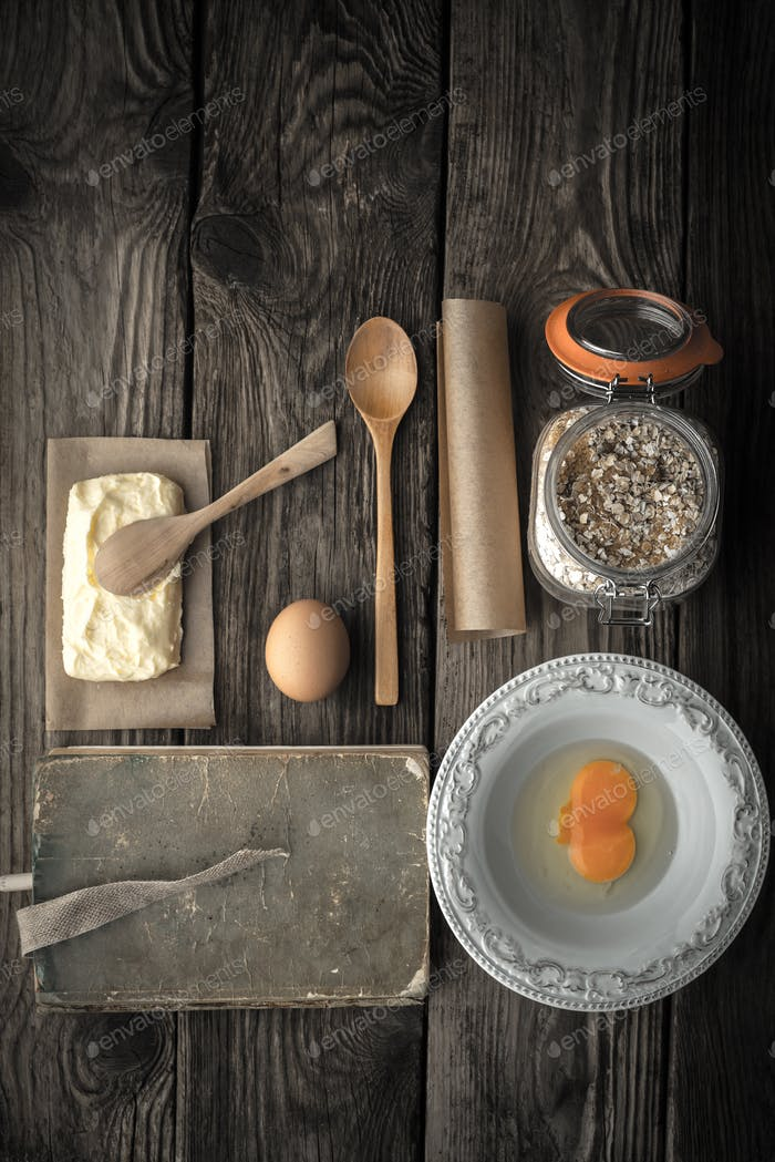 Recipe book, plate and ingredients for cookies on a wooden table