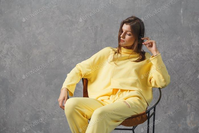 Musik für gute Laune. Junge Frau in gelber Sportbekleidung mit kabellosen Kopfhörern
