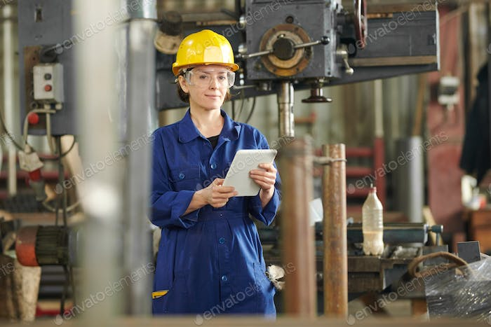 Smiling Woman Using Tablet at Plant