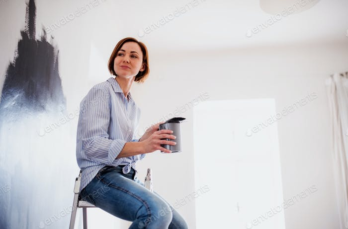 A portrait of young woman painting wall black. A startup of small business.