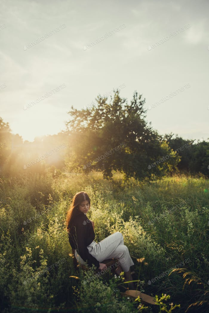 Slow living. Fashionable woman relaxing in summer countryside