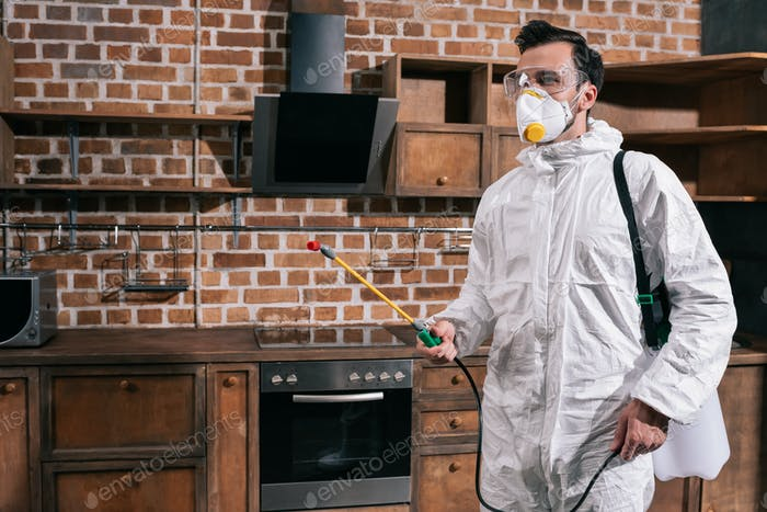 side view of pest control worker standing with sprayer in kitchen