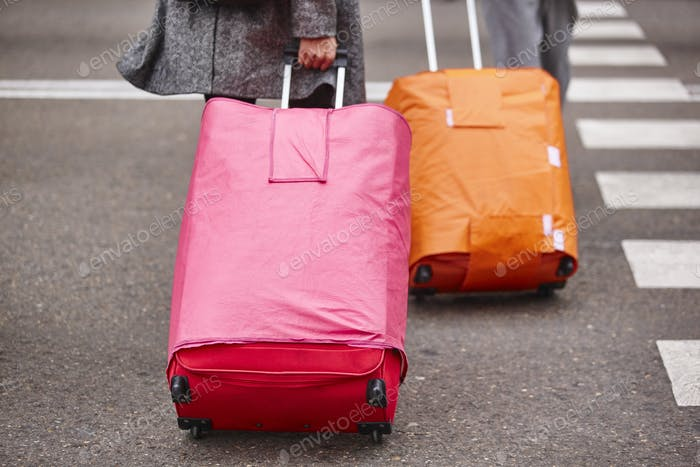 People croosing the street with baggage. Travel tourism background. Horizontal