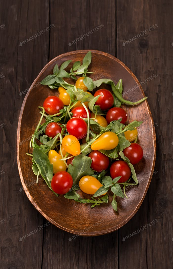 Red and yellow tomatoes on wooden plate