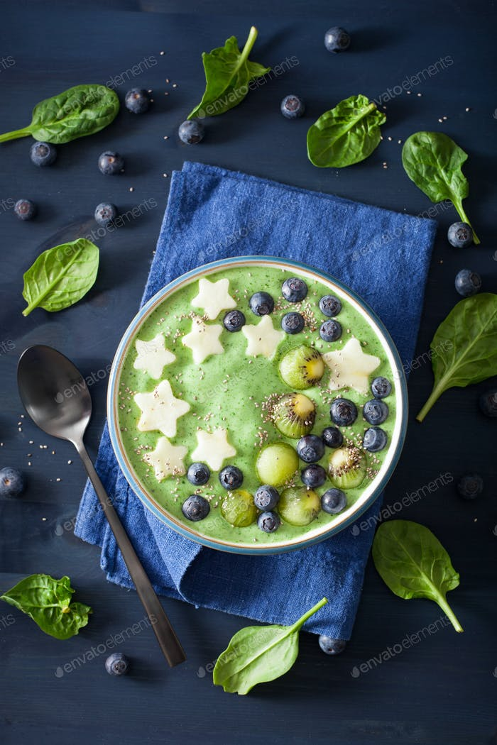 healthy green spinach smoothie bowl with blueberry, apple stars,