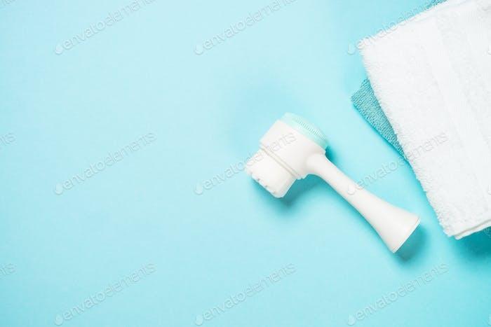 Face massage brush on blue background