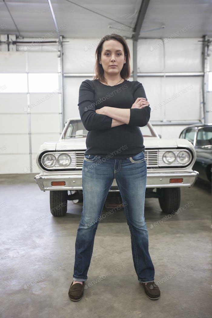 A portrait of a caucasian female mechanic in a car repair shop.