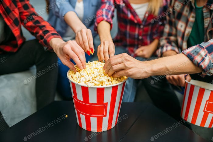 Group of people eating popcorn in cinema