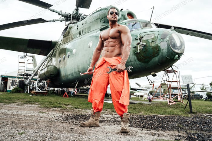 Military technician in airport and soviet war helicopter