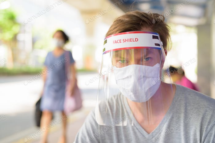 Face of young man with mask and face shield for protection from corona virus outbreak at the bus