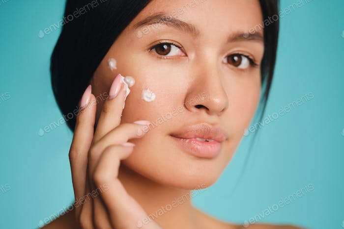 Portrait of pretty Asian brunette girl with points of cream on cheek confidently looking in camera