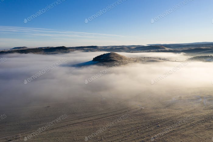 Flying over hills in mystic foggy winter morning. Aerial view by drone