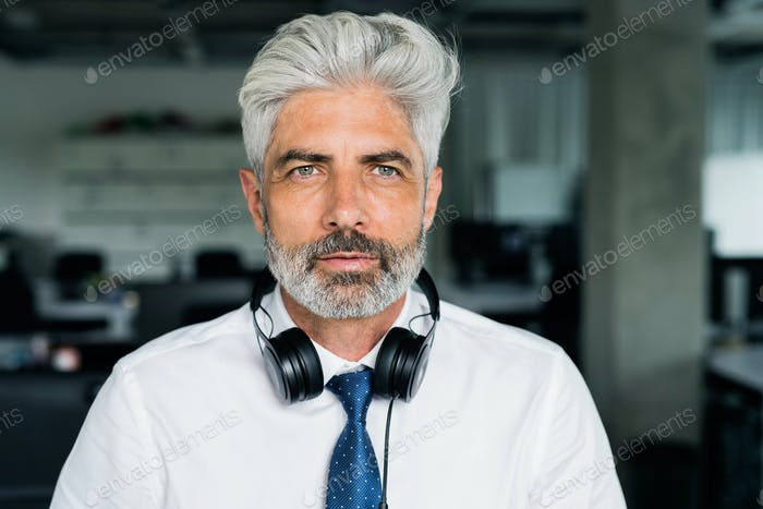 Mature businessman with headphones in the office.