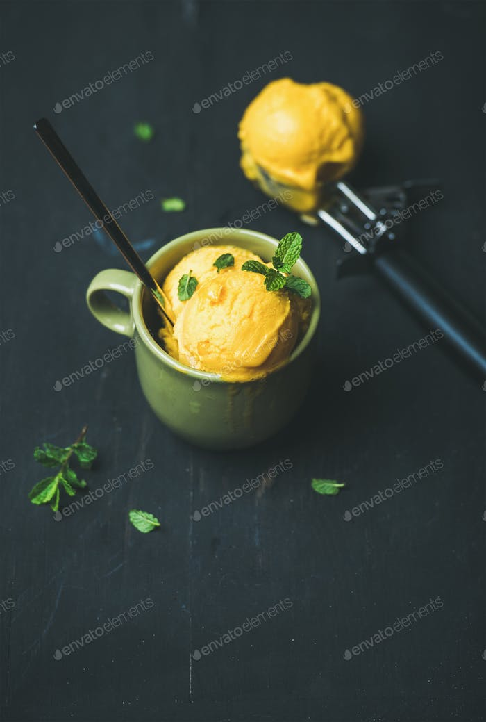 Mango sorbet ice cream scoops with fresh mint in cup