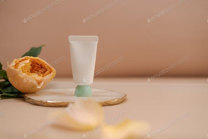 White cosmetic tube on nude minimalist beauty 03