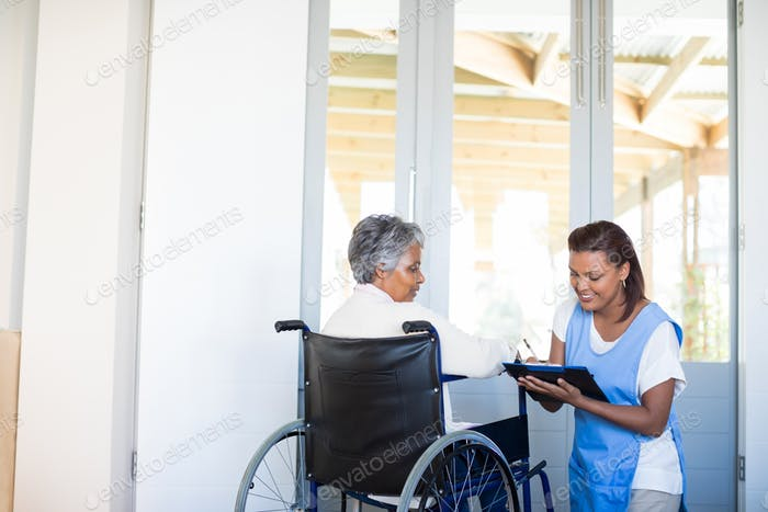 Disability senior woman discussing with female doctor
