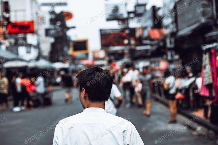 Back view of Portrait Young asian man walking on khaosan road, bangkok