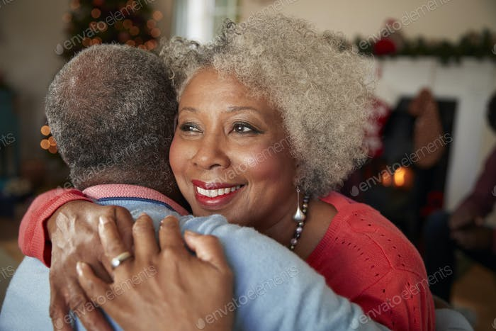 Senior Couple Hugging As They Celebrate Christmas At Home Together