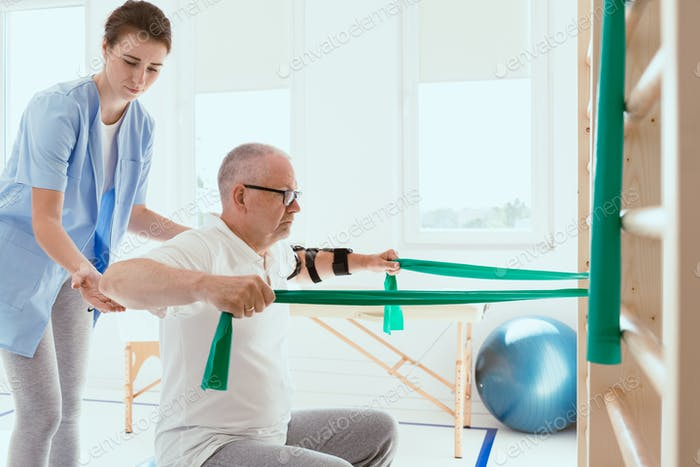 Elderly man doing gymnastic exercises with a young female physiotherapist