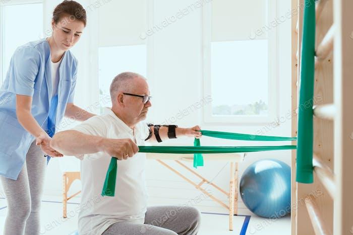 Älterer Mann macht gymnastische Übungen mit einer jungen weiblichen Physiotherapeutin