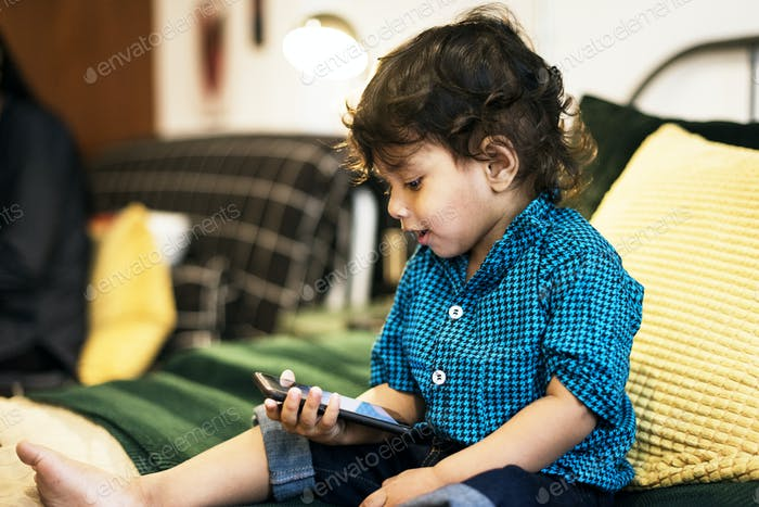 Young Indian boy using mobile phone