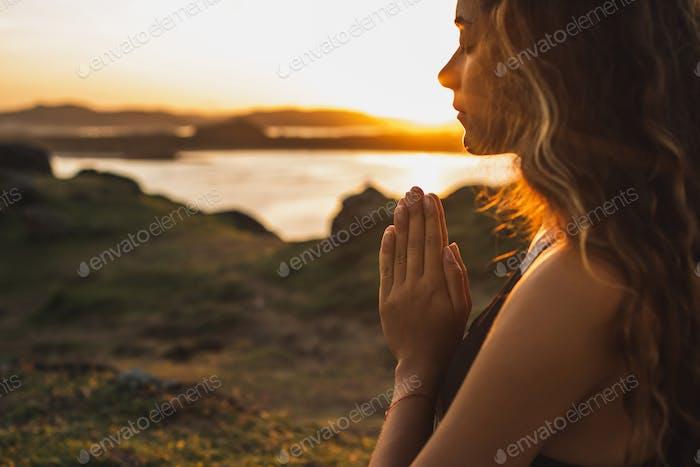 Woman praying alone at sunrise. Nature background. Spiritual and emotional concept. Sensitivity