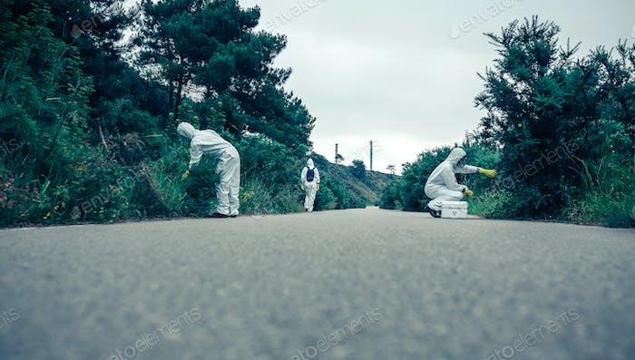 Menschen in bakteriologischen Schutzanzügen auf der Suche nach Proben auf leerer Straße