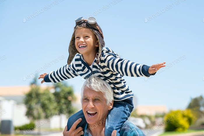 Happy smiling boy flying on shoulder of his grandfather