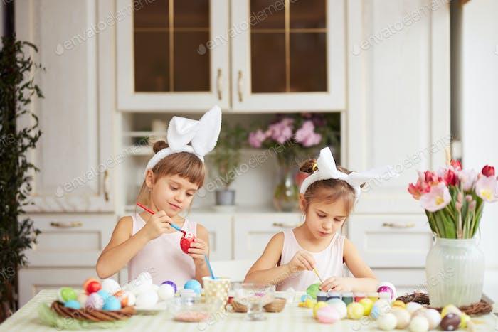 Zwei kleine Schwestern mit weißen Hasenohren auf dem Kopf färben die Eier für den Ostertisch in