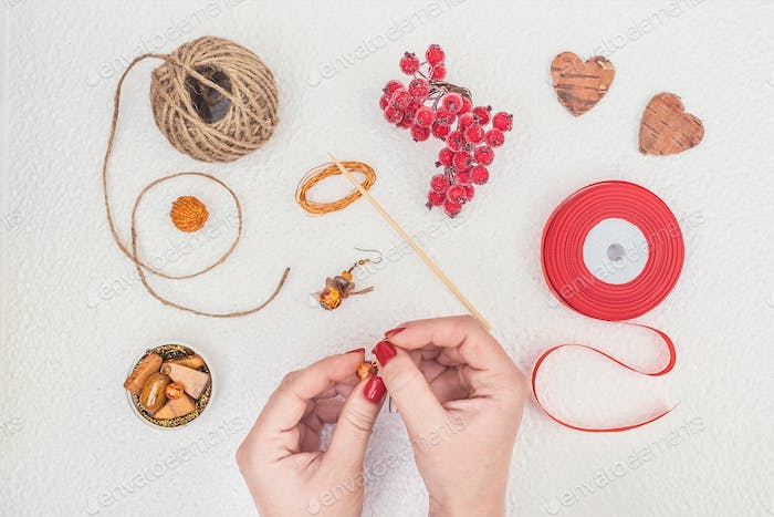 Handmade Jewelry, DIY flat lay in red and brown. Jewelry designer workplace. Woman hands making