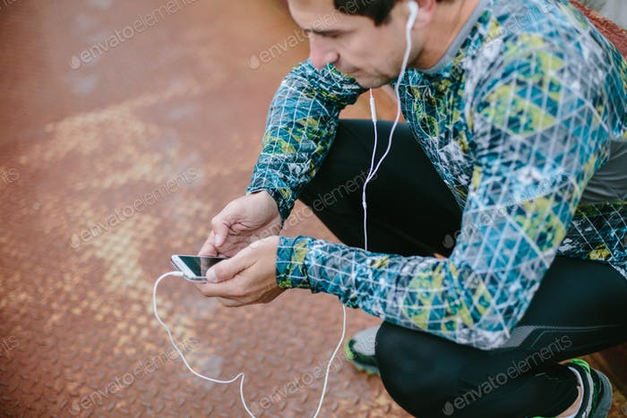 Runner in squat with smart phone and earphones