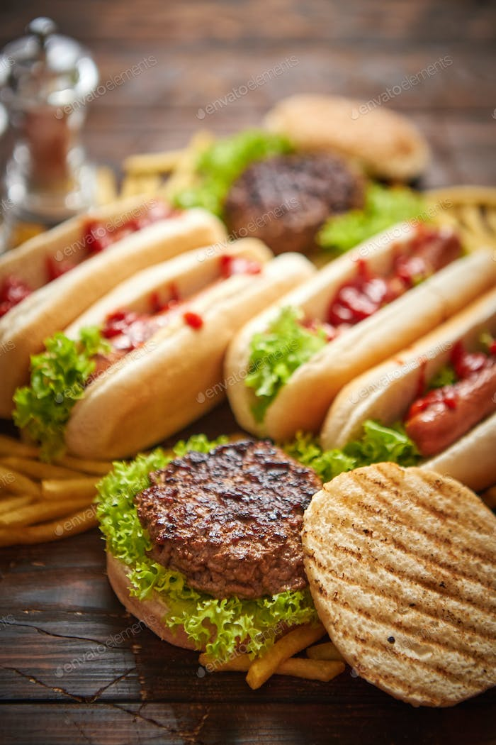 Fastfood assortment. Hamburgers and hot dogs placed on rusty wood table