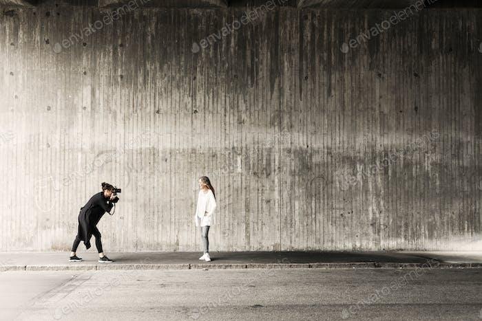Frau fotografieren Freund auf Bürgersteig gegen Wand