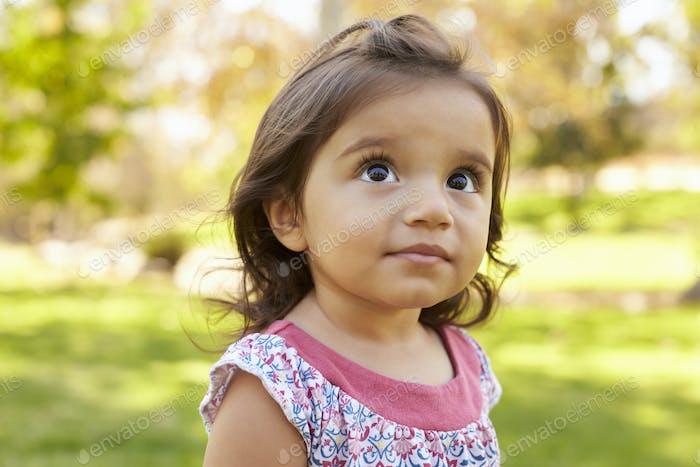 Mixed race Caucasian Asian toddler girl in a park, portrait