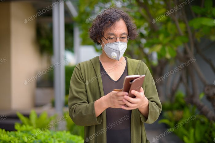 Japanese man with mask using phone in the rooftop garden