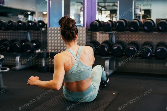 Sporty young female on yoga mat doing situps in gym
