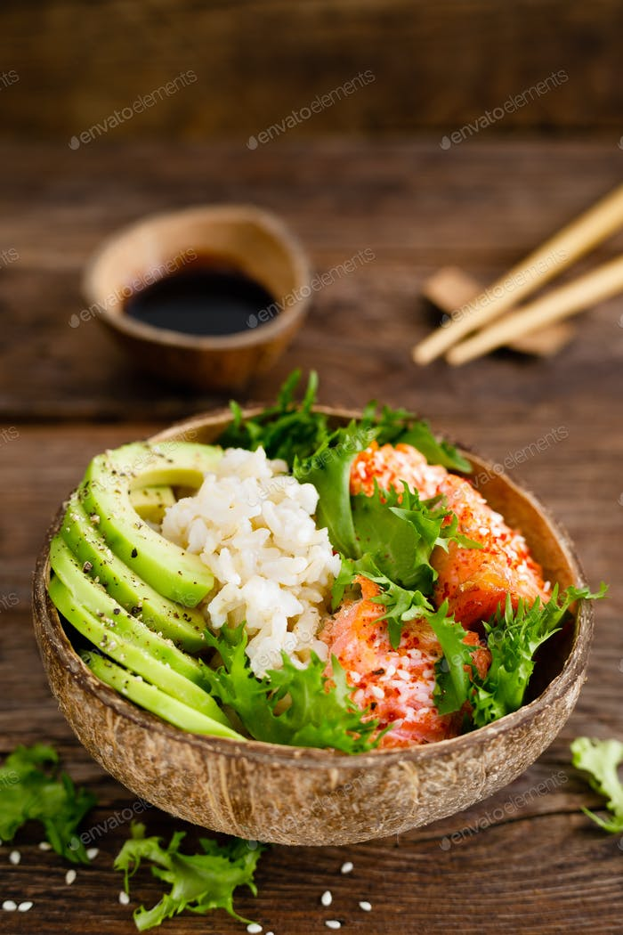 Hawaiian poke coconut bowl with grilled salmon fish, rice and avocado. Healthy food