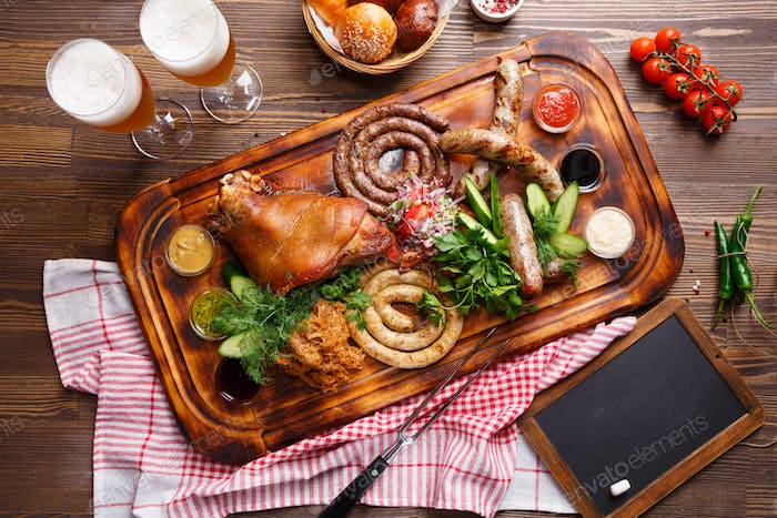 Roast pork and different sausages served with vegetable garnish