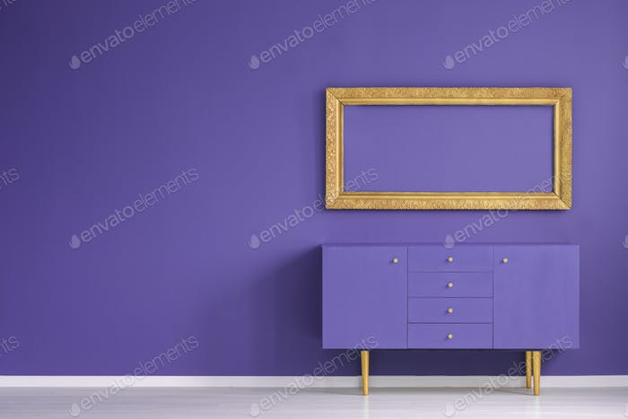 Real photo of a golden frame hanging above a purple cupboard in
