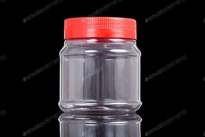 Small translucent plastic PVC jar with red cover isolated in black