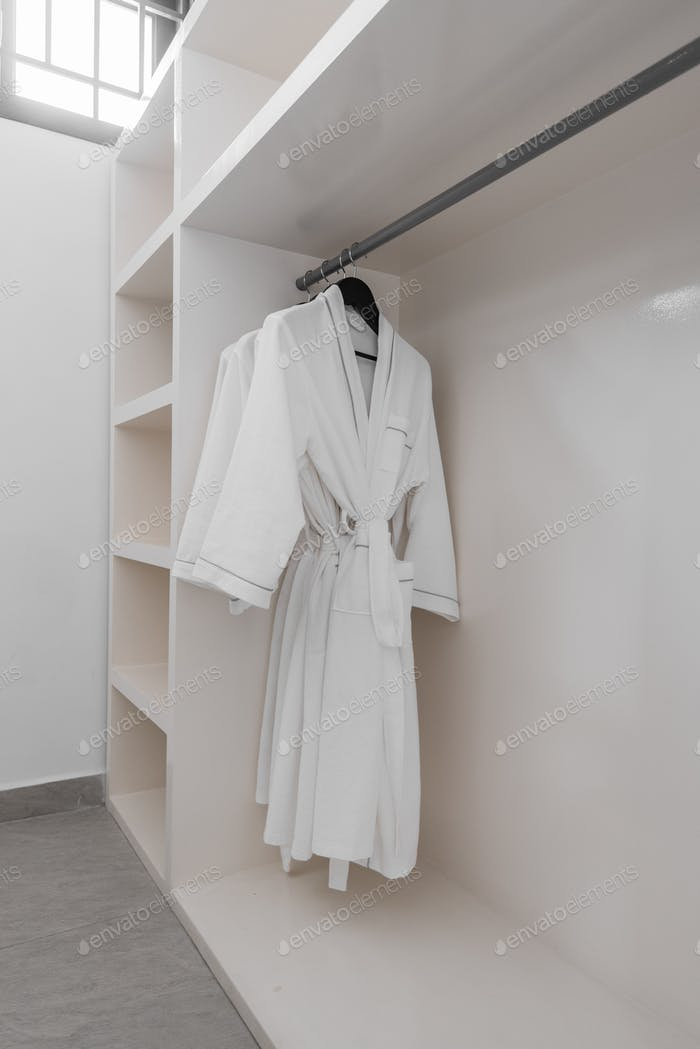 white robes with wooden hangers at dressroom.