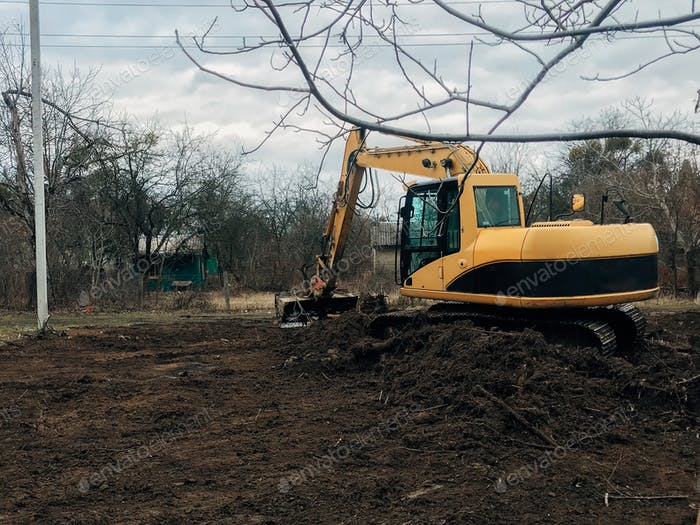 Bulldozer clearing land from old trees, roots and branches with dirt and trash