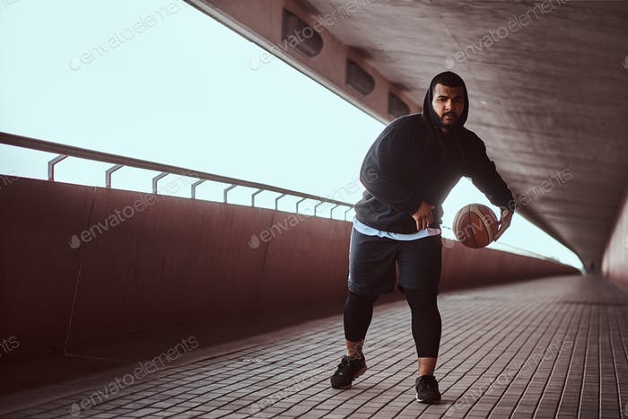 Dark-skinned guy holds a basketball while standing on a footway under bridge.