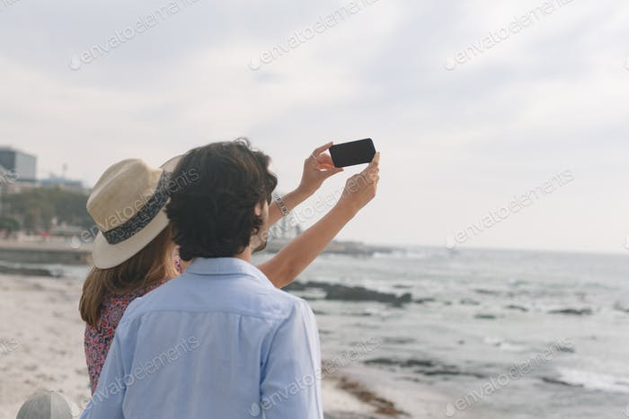 Young Caucasian couple taking selfie with mobile phone while standing near sea side on a sunny day